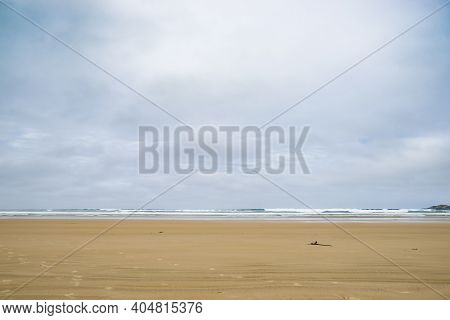 Wide Expansive Flat Beach With Tide Out And Low Waves Breaking On Horizon In Minimalist Style Coasta