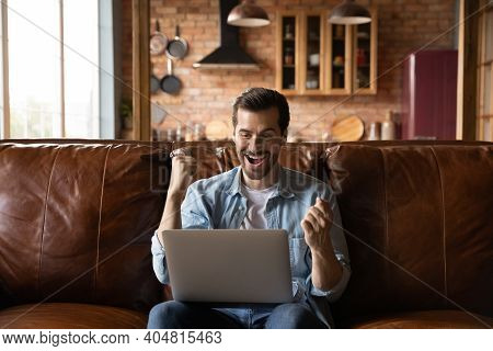 Overjoyed Young Man Triumph With Online Win On Computer