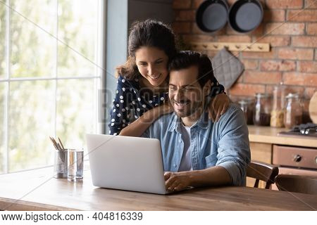 Smiling Couple Use Computer Browsing Internet At Home