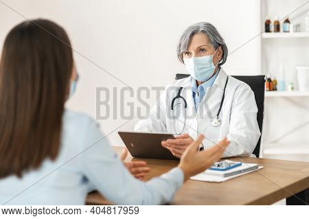Senior Middle-aged Female Doctor In A Lab Coat And A Face Mask Sitting At The Desk, Holding A Touchp