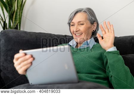 Positive Senior Mature Lady In A Green Jumper Talking Online On The Touchpad, Watching A Webinar, Vi