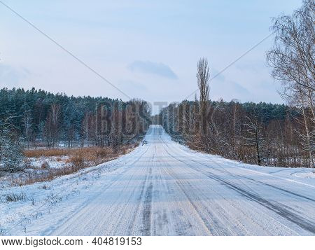 Winter Road In The Snow Leaving The Forest Horizon. Automobile Route. Automobile Highway. White Snow