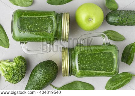 Green Healthy Detox Smoothie With Fresh Vegetables And Fruits In Jars On Concrete Background. Flat L