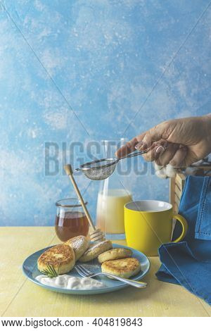 Woman's Hand Sprinkling Sugar Powder Over Cottage Cheese Pancakes, Syrniki, Ricotta Fritters On Cera