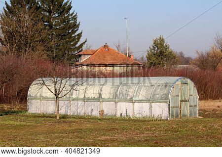 Elongated Plastic Greenhouse With Wooden Doors Covered With Semi-transparent Nylon And Surrounded Gr