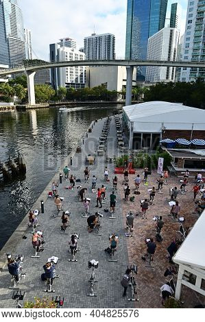 Miami, Florida 01-24-2021 Group Of People Engage In Spinning Class By Miami River On Sunny Winter Mo