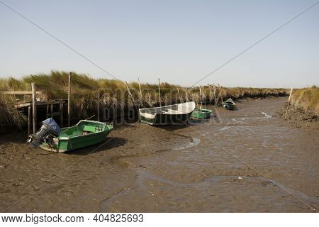 Small Fishing Boats Perched On The Muddy Bottom Of The Canal During Low Tide
