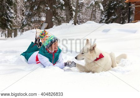 Girl Lying Down With Shepherd Dog On The Snow, Winter Time