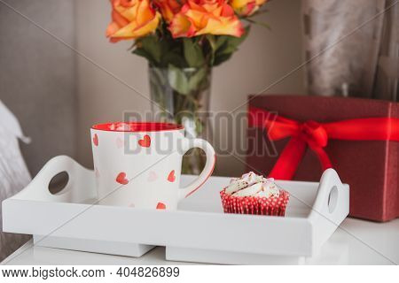 Tray With Fresh Coffee And Cupcake, Gift Box And A Bouquet Of Roses Flowers In Vase On The Bedside T