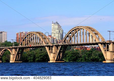Arched Railway Bridge Over The River, Skyscrapers And Towers. Spring, Summer View Of The Dnipro Rive