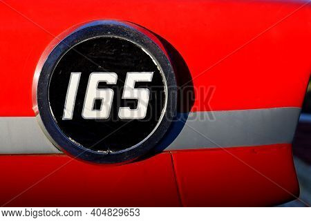 Round Plaque With The Number One Hundred Sixty Five On A Red Background