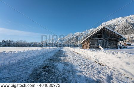 Snow Covered Walking Path Through Sunny Alpine Winter Landscape With Wooden Barn In Wildermieming, T