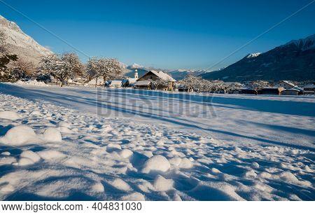 Idyllic Sunny Winter Landscape With Snow Covered Village Church In Austrian Alps, Wildermieming, Tir