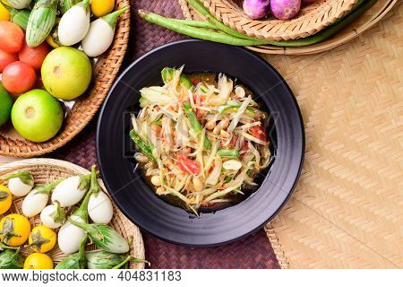 Thai Food (som Tum), Spicy Green Papaya Salad With Vegetables On Woven Bamboo Background, Top View