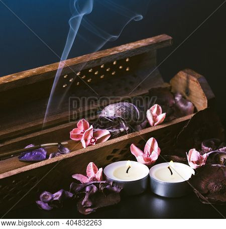 incense stick aroma with smoke  in a wooden handmade holder with dried petals and candles  isolated on background