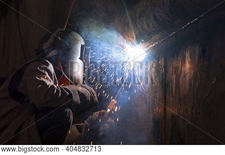 Welder In Welding Mask Is Welding Metal Wall Of The Old Fishing Vessel At Shipyard In Dark Tone Styl
