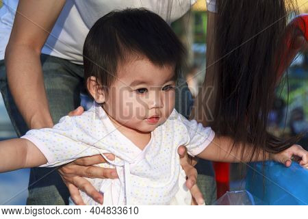 Hands Of Mother Holding Daughter At Playground Outdoor. Happy Baby Girl Play At Park With Mother Han