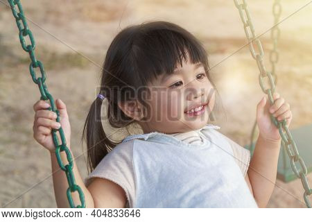 Close Up Cute Little Girl Having Fun On Play Swing In Playground On Warm And Sunny Day Outdoors. Asi