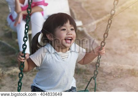 Cute Little Girl Having Fun On Play Swing In Playground On Warm And Sunny Day Outdoors. Asian Girl H