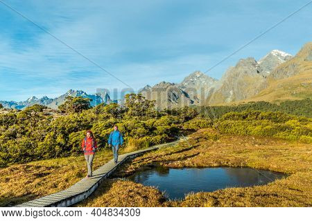New Zealand Hiking. Young hiking couple walking on trail at Routeburn Track during sunny day. Hikers are carrying backpacks while tramping Key Summit Track in Fiordland National Park in New Zealand.