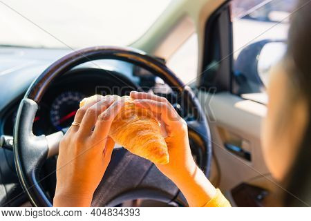 Asian Woman Eating Food Fastfood While Driving The Car In The Morning During Going To Work On Highwa