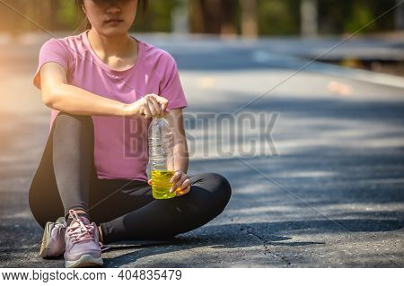 Close-up Of Woman Sport Athletes And Electrolytes. Asian Woman Dehydrated Sweating After Outdoor Run