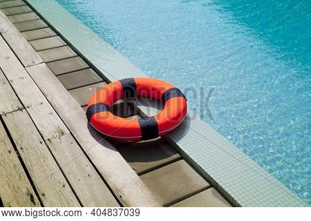 The Red Life Ring Lies On The Wooden Floor Of The Swimming Pool.