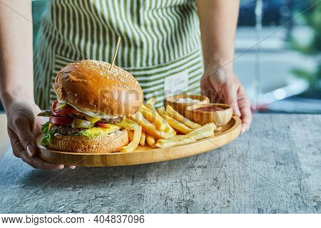 Hands Holding A Wooden Plate With Burger And Fry Potato With Ketchup And Mayonnaise