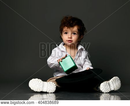 Stylish Baby Boy. Toddler Child Model Wearing Casual Apparel, Shoes Putting Toy Building Block Into