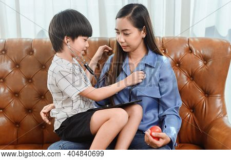 Asian Family Togetherness At Home. Mom And Kid Playing As Doctor Together In Living Room. Lifestyle
