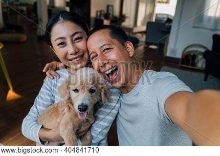 Young Adult Asian Couple Holding A Puppy Taking A Selfie From A Phone With Home Interior In Backgrou
