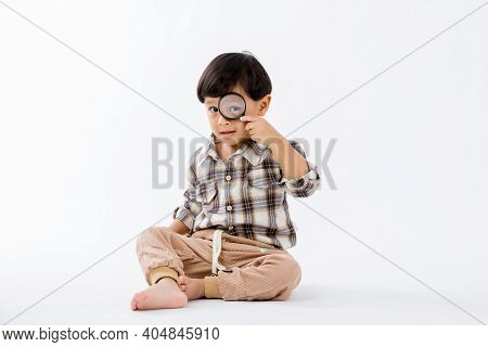 Child Holding Magnifying Glass On White Background. Boy With A Magnifying Glass In Studio.