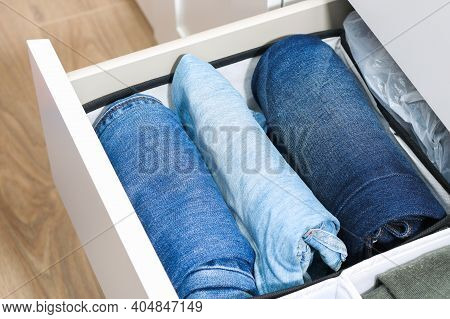 Man Takes Trousers Folded By The Method Of Marie Kondo. Vertical Storage Of Clothes In A Chest Of Dr