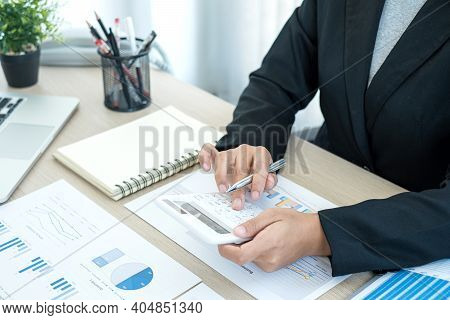 The Businesswoman Hand Sits At Their Desks And Calculates Financial Graphs Showing The Results Of Th