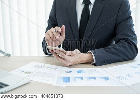 The Businessman Hand Sits At Their Desks And Calculates Financial Graphs Showing The Results Of Thei