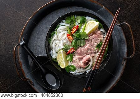 Pho Bo Vietnamese Soup With Beef And Rice Noodles On A Dark Background, Top View