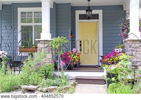 Yellow front door of a small house in the suburbs of Canada. Attractive and colorful front porch surrounded by perennial and annual flowers in summer.