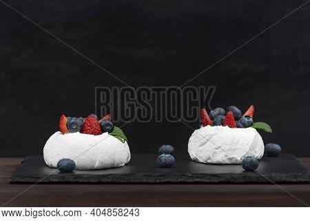 Anna Pavlova Cake On Black Background. Air Meringue Cake With Fresh Strawberry And Blueberry.
