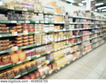 Blurred Supermarket Aisle With Colorful Food Shelves Of Merchandise. Perspective View Of Abstract Su