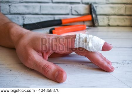 Bandaged Finger On Workers Hand. An Accident At Work - Bandaging Mans Injured Finger. Hand With Band