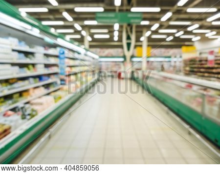 Blurred Supermarket Aisle With Colorful Refregirator Shelves Of Merchandise. Perspective View Of Abs