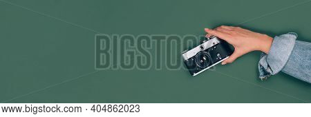 Banner With Female Hand Holding Old Vintage Photo Camera On Green Background With Copy Space For Tex