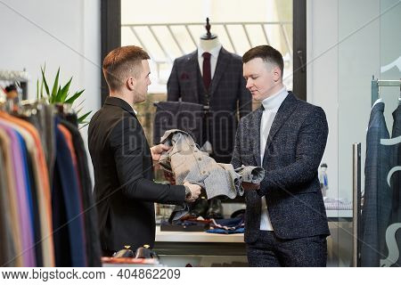 A Stylish Man In A White Turtleneck Sweater And A Suit Is Listening To A Shop Assistant About A Shir
