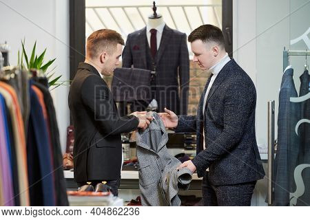 A Stylish Shop Assistant Is Talking To A Man In A White Turtleneck Sweater And A Suit About A Shirt