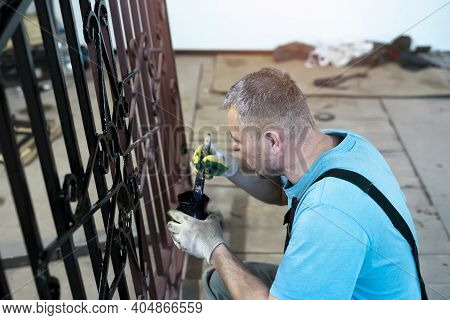 A Man Paints A Hand-made Wrought-iron Fence.