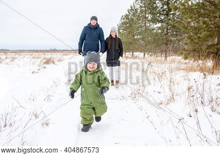 Cheerful Child Runs In The Winter In The Snow Ahead, And His Parents Follow Him. The Family Walks In