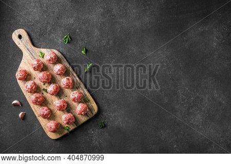 Raw Meatballs On Black Background, Top View, Copy Space. Beef Meatballs On Wooden Board  Ready For C