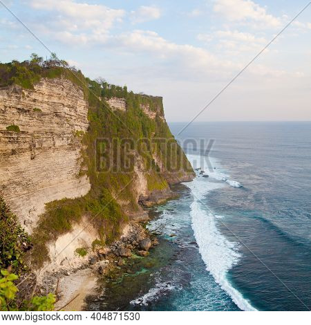 View Of Uluwatu Cliff With Blue Sea In Bali, Indonesia. Rocky Cliff And Sea Waves, Top View.