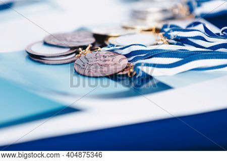 A Bunch Of Marathon Finisher's Medals Lying On Certificate. Race Running Medals From Marathon On Blu