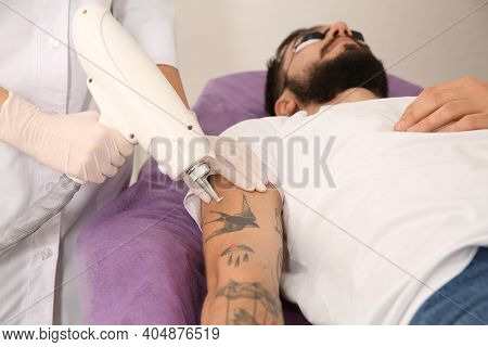 Young Man Undergoing Laser Tattoo Removal Procedure In Salon
